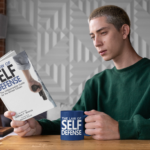 mockup-of-a-man-drinking-from-a-two-toned-coffee-mug-while-reading-a-book-28454